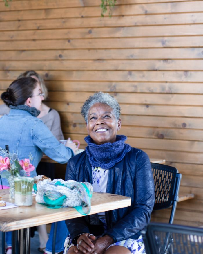 A woman sits in a coffee shop and smiles up at the ceiling. She is wearing a purple leather jacket and a Marilue Cowl in navy.